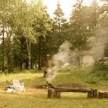 Au lever, le feu fume encore malgré la pluie qui s'est abattue sur la fête pendant une partie de la nuit. Un lendemain de veille respectable!